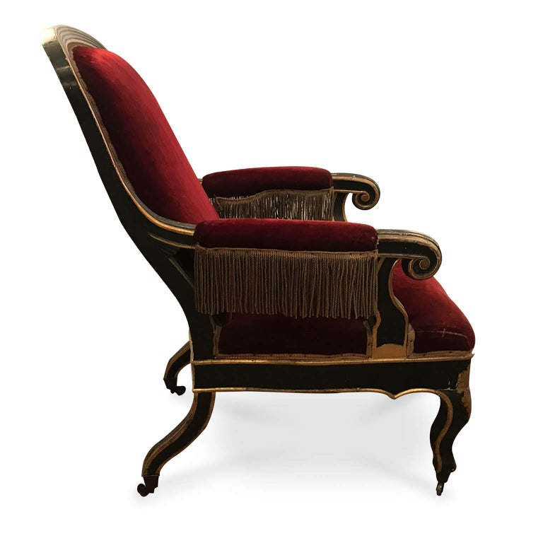 Antique Italian armchair from Sicily with footrest, a Louis Philippe poplar armchair dating back to the last quarter of 19th century, with a dark lacquer wooden frame decorated with an elegant vegetal gilded motif and gilded profiles.  Elegant