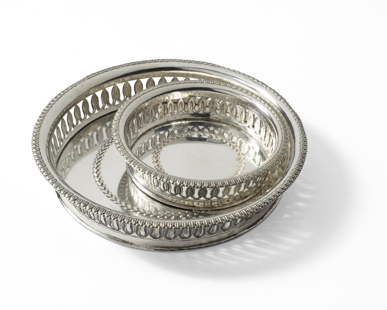 Twelve silver glass coasters and four silver wine coasters. Silversmith Antonio Mantelli Milan, circa 1830 They measure: Glass coasters: 0.78 in high x 3.46 in diameter (2 cm x 8.8 cm) Wine coasters: 0.86 in high x 5.24 in diameter (cm 2.2 e cm