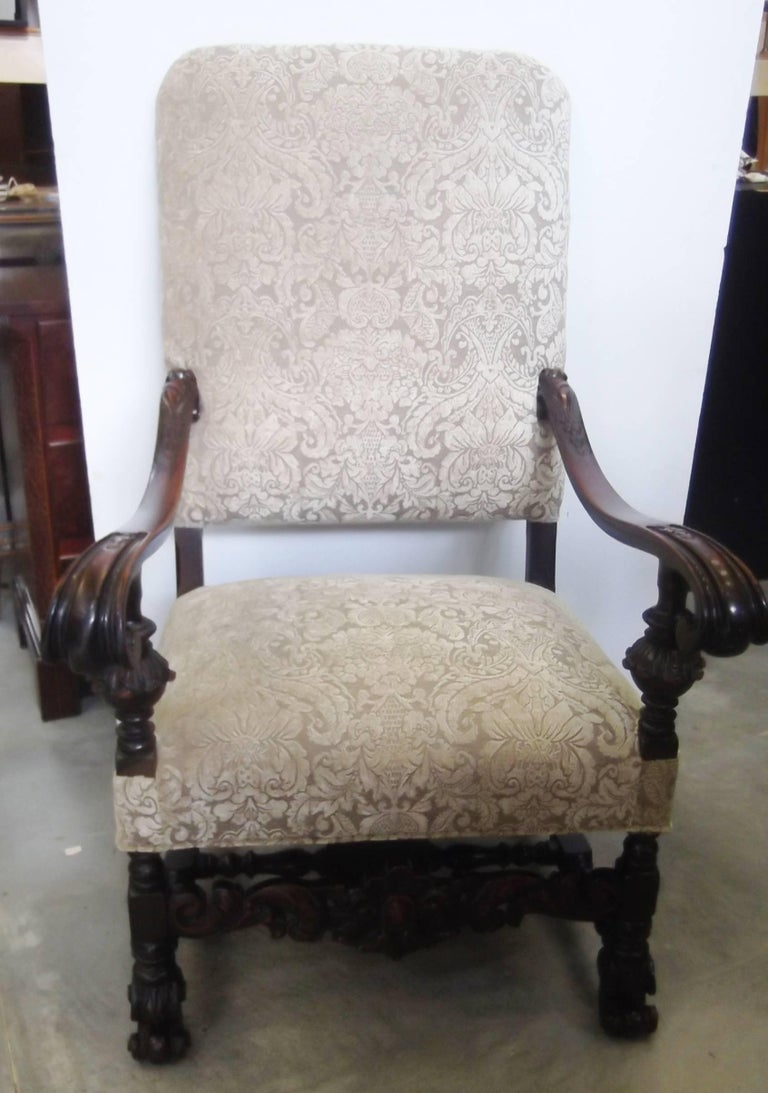 Impressive and stately English throne armchair with shapely scrolled arms. The detailed frame is hand carved and has a nice patination to the wood from decades of well cared for use. The new fabric is a damask chenille in a neutral mushroom color.