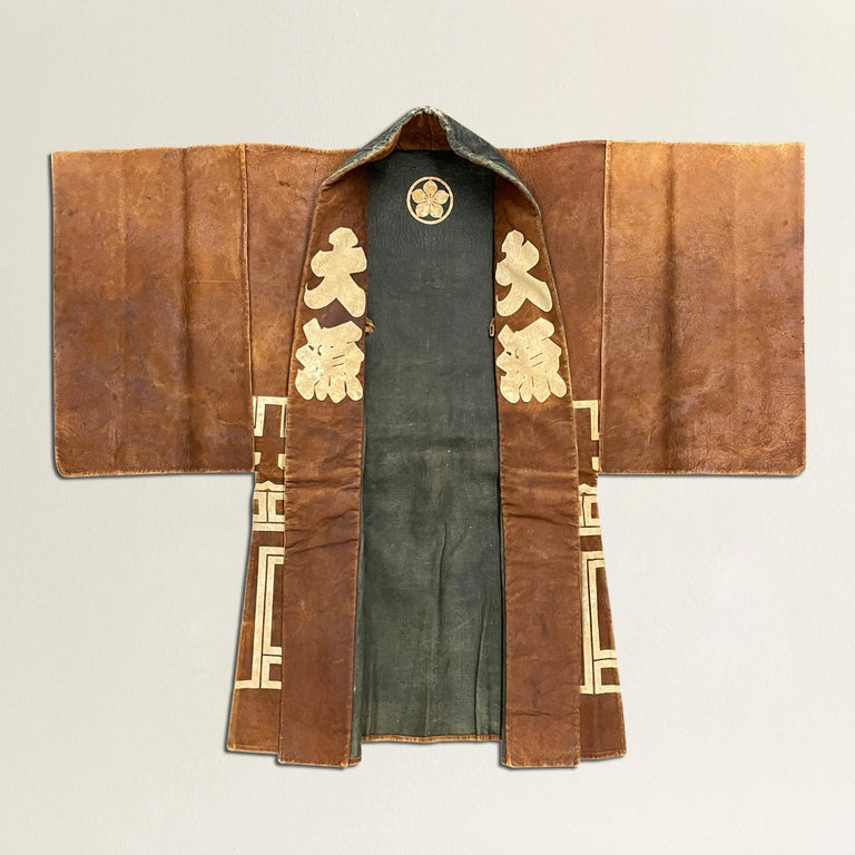 A rare 19th century Japanese firemen's coat, constructed from smoked deer leather and with bold white stenciled characters creating a wonderfully modern pattern across the back and bottom portion of the coat. The interior is black and white with