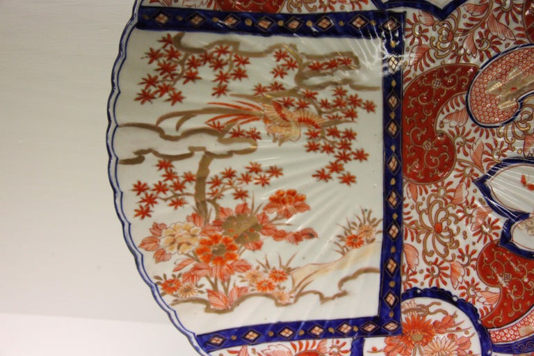 19th century Japanese Imari charger with scalloped edge, all-over floral pattern interspersed with multi shaped panels filled flowers and dragonflies.