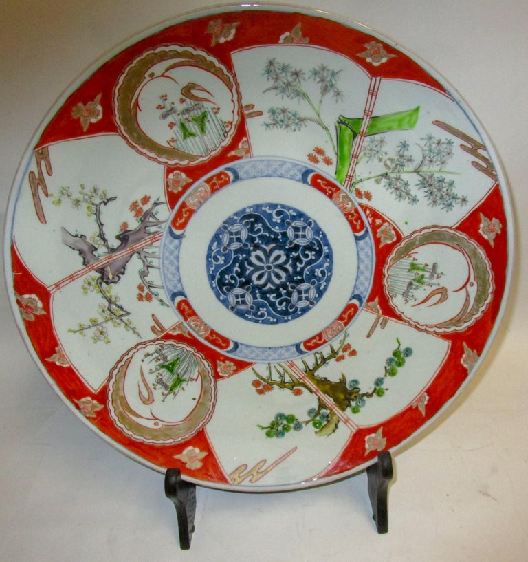 This handsome Japanese Porcelain charger dating from the Meiji era (1868-1912) is boldly hand painted with deep rich blue and cinnabar enamel with unusual green accents. The platter features a blue center medallion, various other designs and