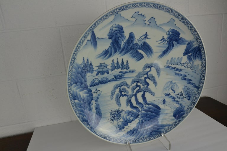 A large blue and white Japanese platter from the late 19th century. Decorated with a landscape scene with trees, hills and homes. Nice blue tint the white ground.