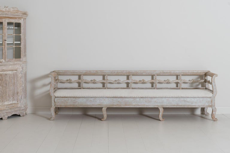 A very long sofa bench from the Karl Johan period in original paint with a newly upholstered seat.
