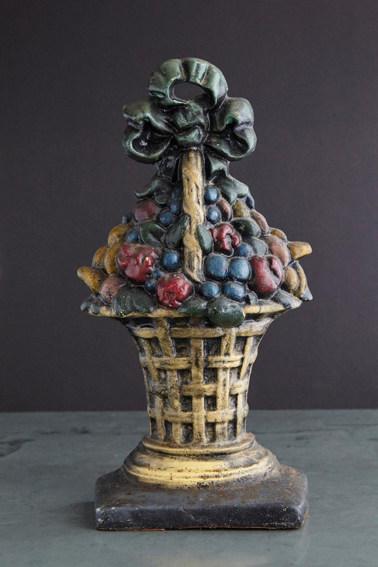 Lovely late 19th century large cast iron hand painted polychrome flower bouquet in basket doorstop with it's original paint and fantastic patina. Heavy, solid piece of iron.