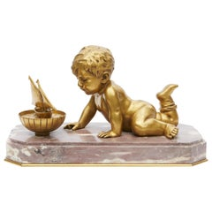 19th Century Large Gilt Bronze Cherub Playing with His Toy Boat on a Marble Base