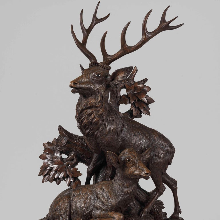 A large Black Forest mantle clock  Constructed in carved linden wood, fitted with a two train 8 day striking clock movement; mounted on a shaped branchwork base, the naturalistic ground of rockwork, tree branches, oak leaves and ferns surrounding