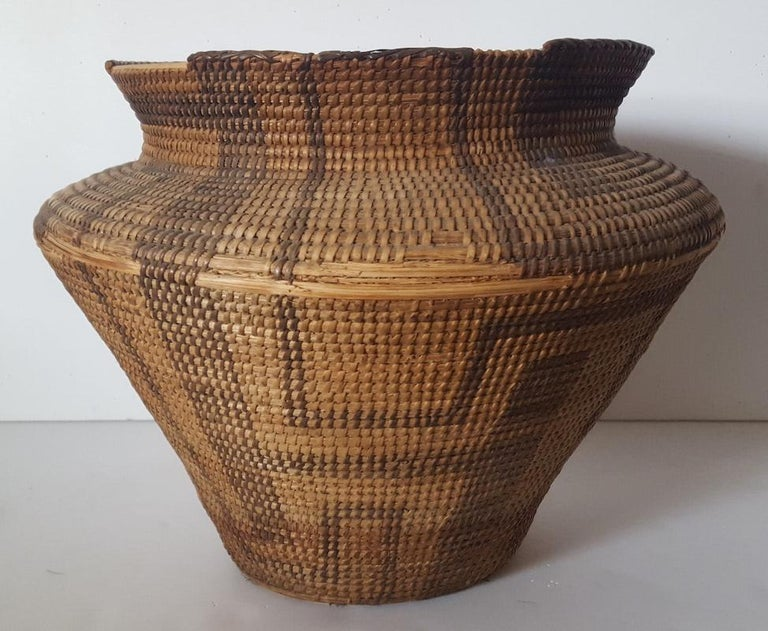 This large, hand woven basket, likely Pima-Papago, or similar Southwestern Native American Tribe, is in worn condition from much use, and has lost it's symmetrical shape. It lists or leans a bit to one side and has several losses of woven grasses on