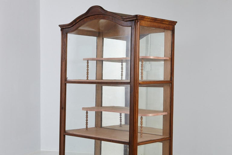 A lovely and light walnut cabinet/vitrine, with one original large glass door, glass side panels, and a mirrored back. Two large shelves with two recessed half shelves covered in fabric and a hand carved bonnet. The key is present, just not on the