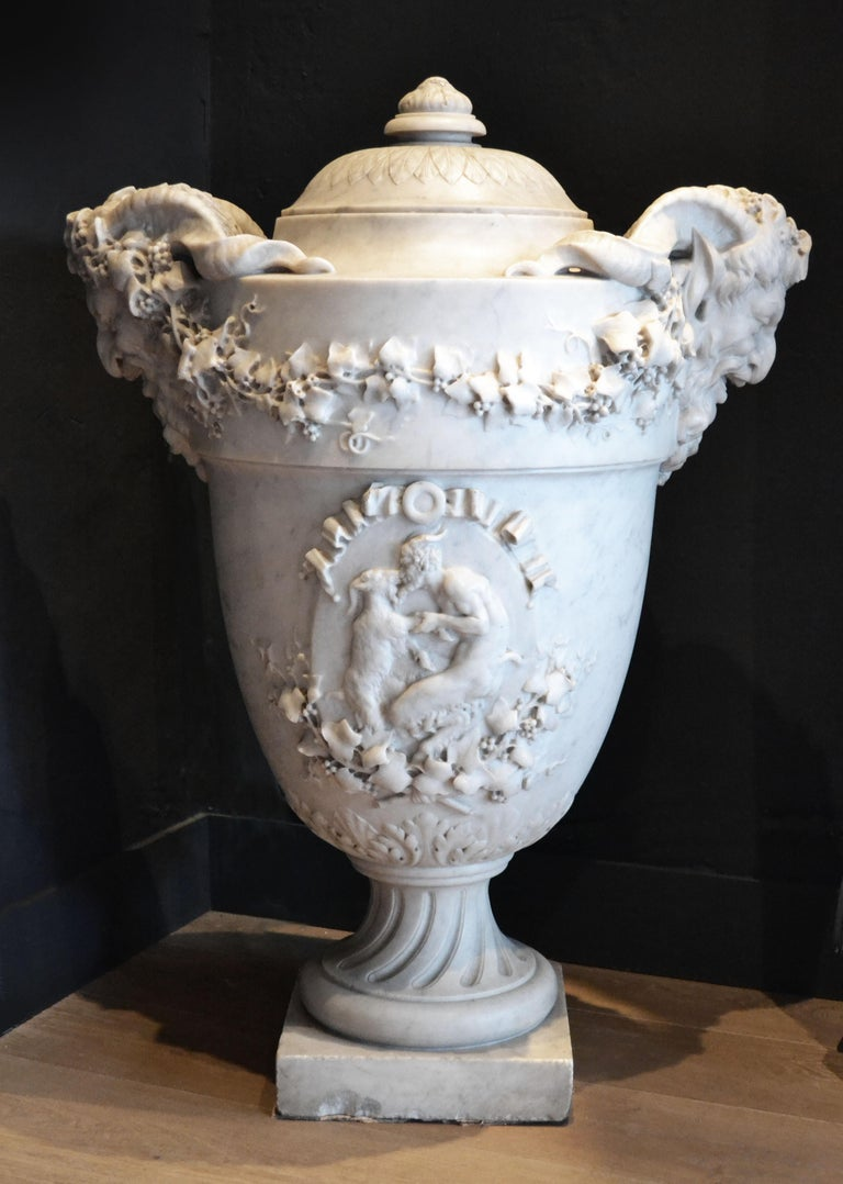 An impressive 19th century Carrara marble lidded company urn. The fine quality carving depicts a dancing faun and the urn is flanked by two satire heads draped with ivy leaf decoration.