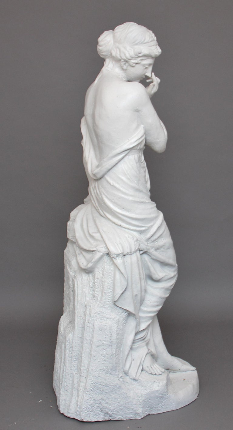 A life-size French mid-19th century cast iron statue of a semi clad pretty maiden wearing Classical Greek costume, standing over a broken jug whilst leaning on a wall, circa 1860.