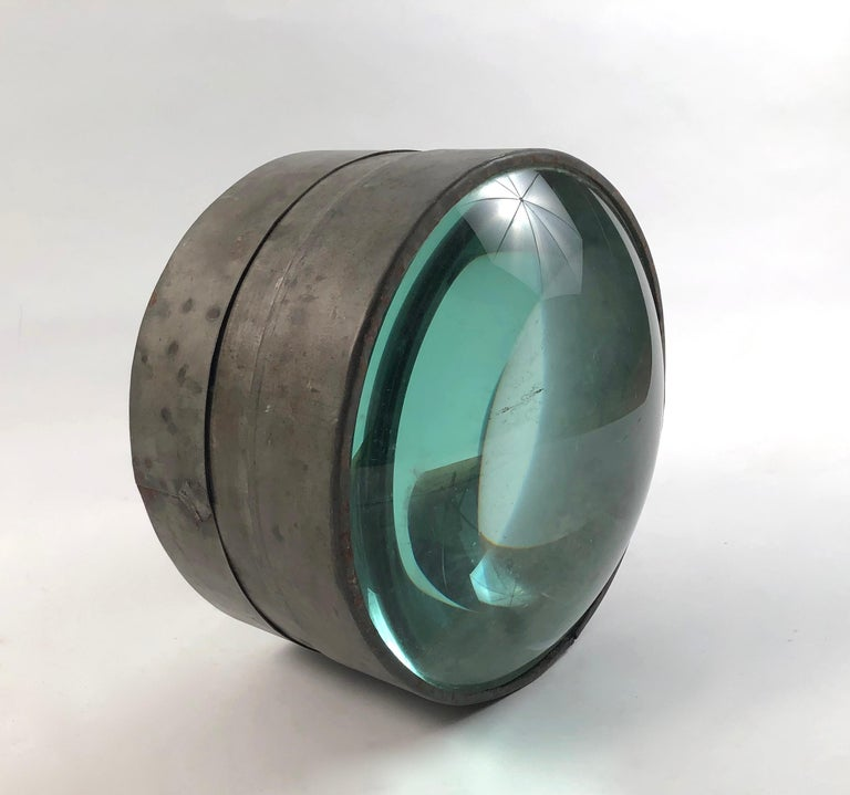 A rare 19th century light house lens, American, circa 1880s, the 2 magnifying convex glass elements contained in a tin or zinc band. This uncommon and beautiful object, both nautical and scientific is a unique tabletop or bookshelf sculpture that