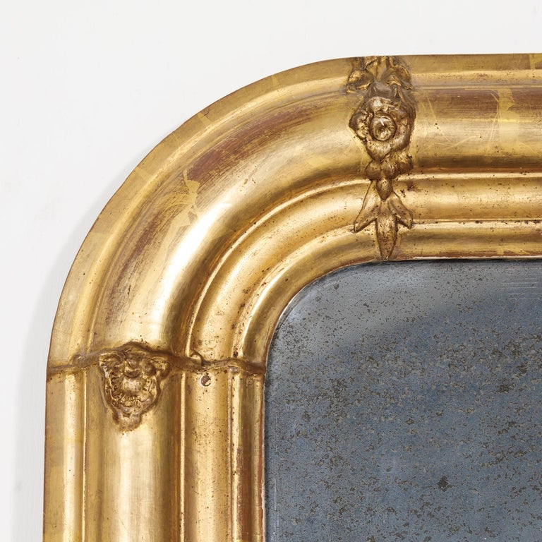 19th century French period Louis Philippe giltwood mirror adorned with floral and foliate carvings, having its original mercury glass, circa 1830s.The rectangular shape of the frame has straight corners at the base, while the upper shoulders have