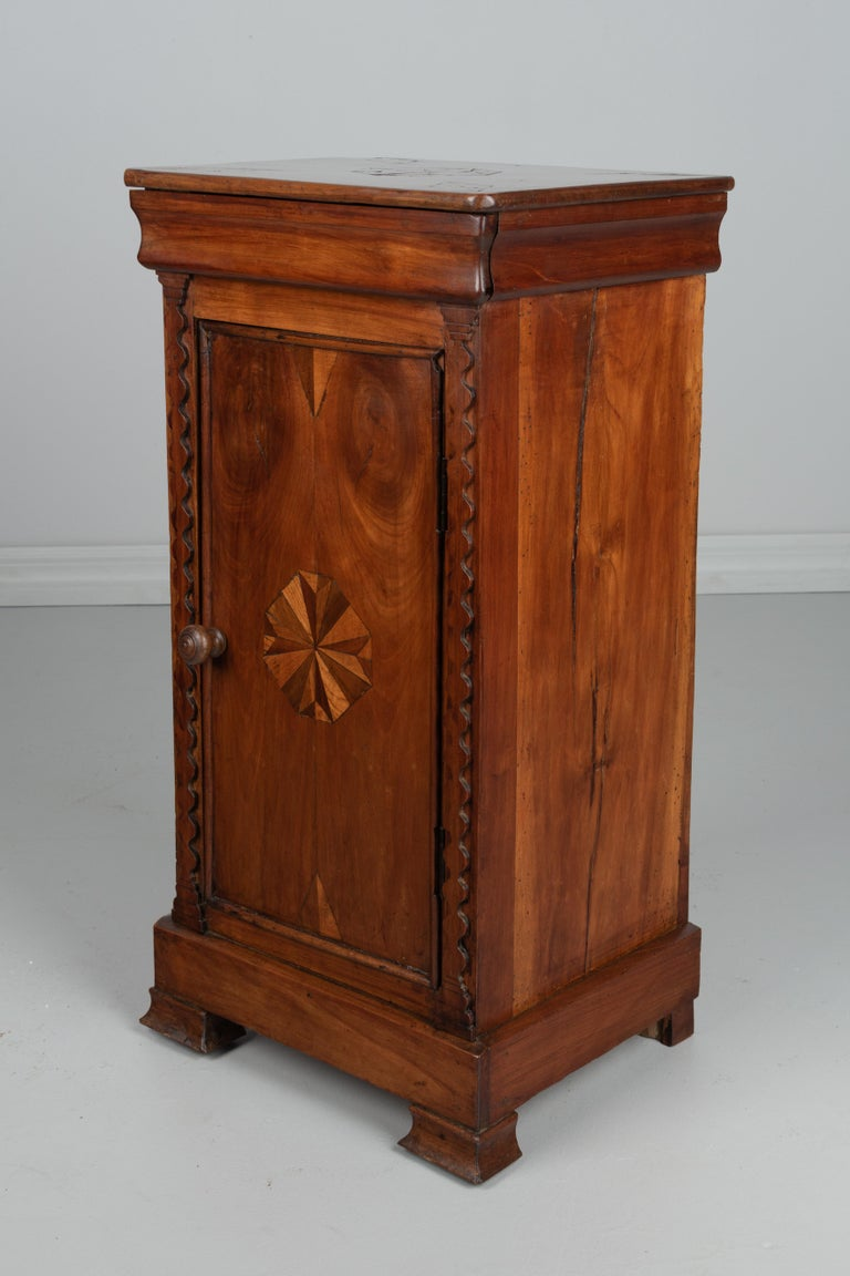 An early 19th century French Louis Philippe nightstand or side table made of solid cherry with simple marquetry inlaid decoration. Hidden drawer above a cabinet door. One interior shelf. Finely crafted for a country table. Waxed finish. Minor