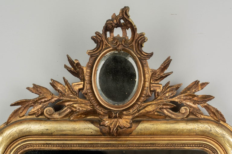 A 19th century Louis Philippe style giltwood mirror with oval mirrored crest surrounded by gilded leaves. Curved top corners, bright gilt with incised decoration, bead border, bottom corner decoration. Original mirror. Losses and repairs to the