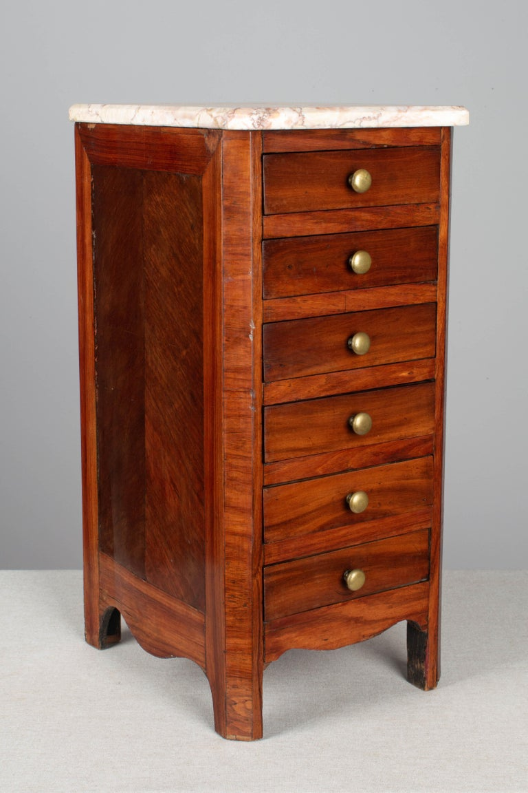 A 19th century Louis Philippe style miniature sample commode made of solid and veneer of mahogany with French polish finish. Five dovetailed drawers with brass knobs. Unusual tall, deep proportions. Replaced marble top is not attached. Minor veneer