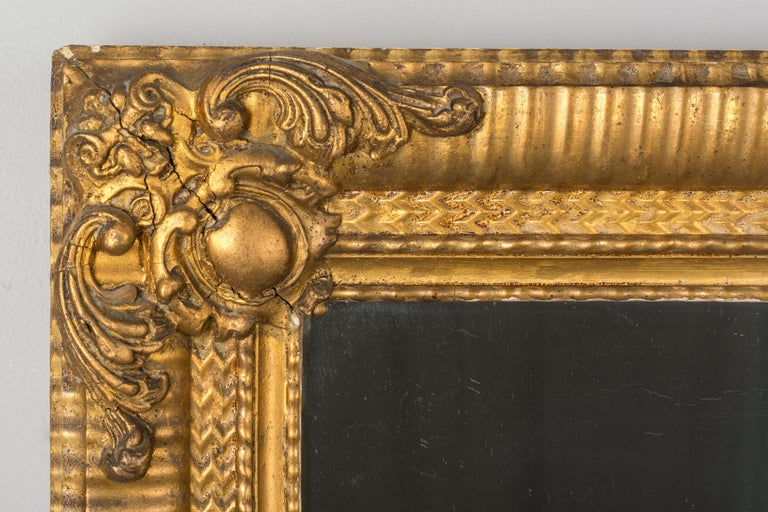 A 19th century French Louis Philippe style giltwood and gesso mirror with three inch wide ribbed frame and corner decorations. Warm gilt finish. Original mirror with old silvering. Minor loss to gilt. Can be hung horizontally or vertically. The