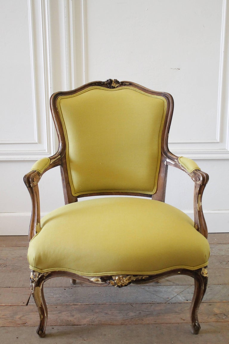 """19th century Louis XV style fauteuil in chartreuse linen Beautiful antique frame, with chippy painted patina, exposing the wood frame, and traces of gilt. Measures: 26"""" W x 35"""" H x 26"""" D, seat H 17"""" x seat D 20"""" x arm H 23""""."""
