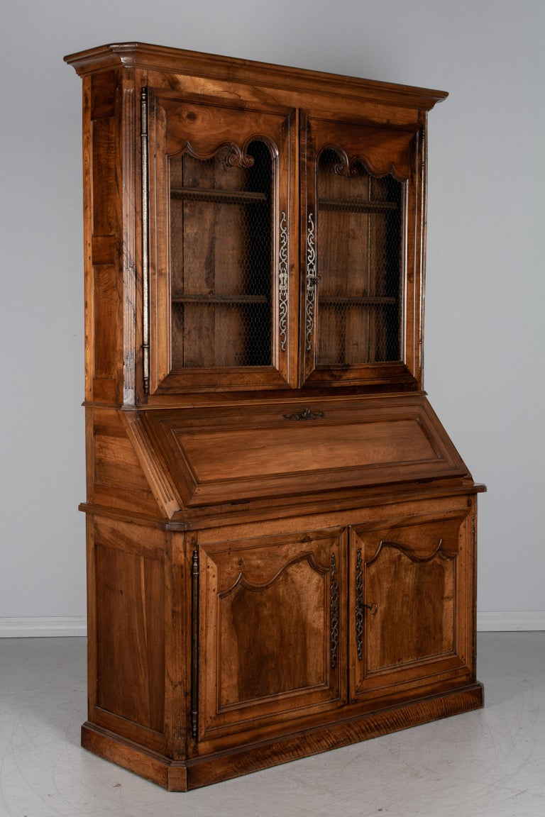 An exceptional 19th century French Louis XV style scriban, or secretary, from the Loire Valley, made of solid walnut with pegged construction and mortise and tenon joints. The abbattant, or slant front desk, hinges open to reveal a leather writing
