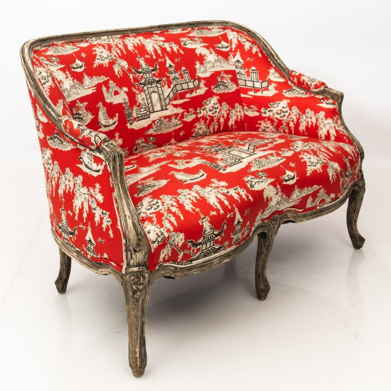 Louis XVI style French settee newly upholstered in chinoiserie red fabric. Berger style frame resting on a six legged support with scrolled arms and cabriole legs.