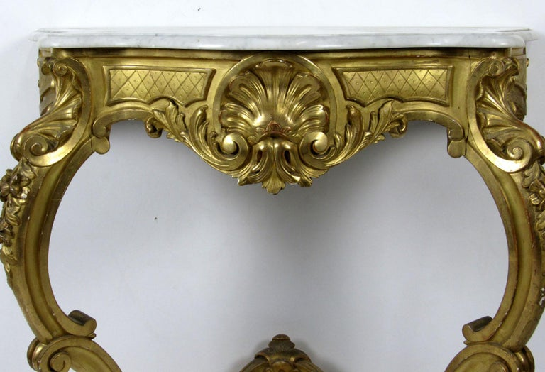 Louis XV style two-legged wall console with original Carrara white marble top, ornate apron and trestle carved with delicate shells.