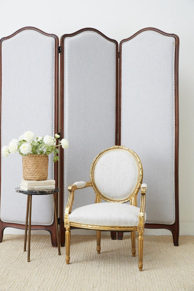 Distinctive 19th century carved walnut three panel folding screen featuring a French ticking stripe upholstery. Made in the French Louis XV taste with a domed crest and shaped feet. The stripe pattern fabric is beautifully laid with a double welt