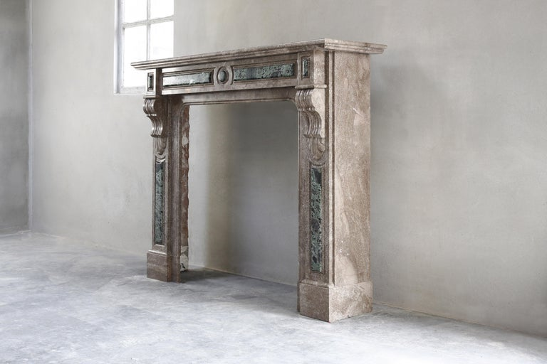 Beautiful decorative antique fireplace made of marble in the style of Louis XVI. This fireplace dates from the 19th century and consists of the green marble type Tinos and the brown marble type Emperador. A beautiful fireplace and unique of its