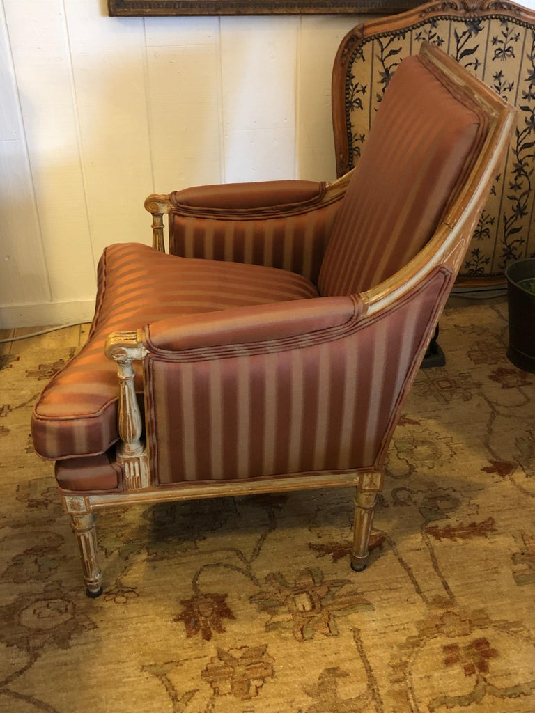 A Classic French bergère having carved Louis XVI style light wood frame with original whitewashed paint, later upholstered with top of the line Rose Tarlow fabric and down seat cushion. Pretty front and back.
