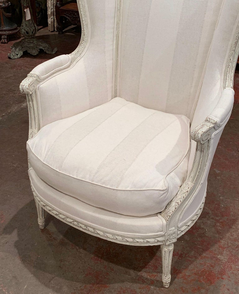 Decorate a bedroom or den with this elegant antique armchair. Crafted in France circa 1880, the chair sits on delicate tapered legs over a carved apron. The tall curved back is embellished with ear shaped sides and the armrests are decorated with