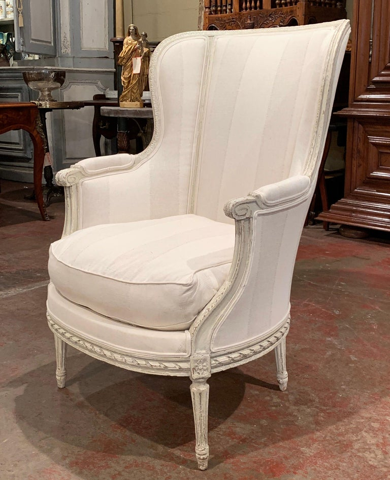 French 19th Century Louis XVI Carved Painted Bergère Armchair with Striped Fabric For Sale