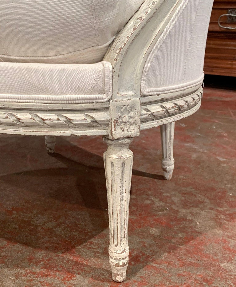 Patinated 19th Century Louis XVI Carved Painted Bergère Armchair with Striped Fabric For Sale