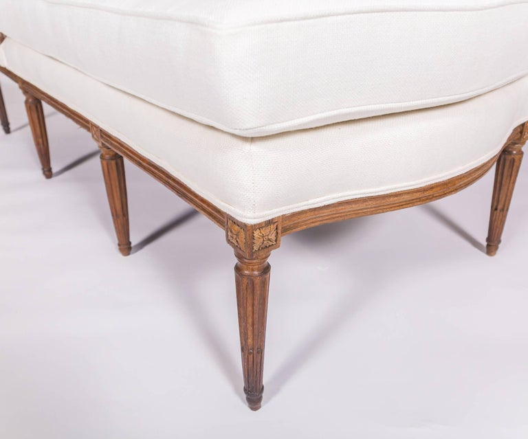 19c French Louis XVI chaise. Lovely wooden chaise in white upholstery. Carved wooden frame and legs in polished walnut wood. Wear consistent with age and use. Wood shows wear and scratches.   Measures: approximately 78