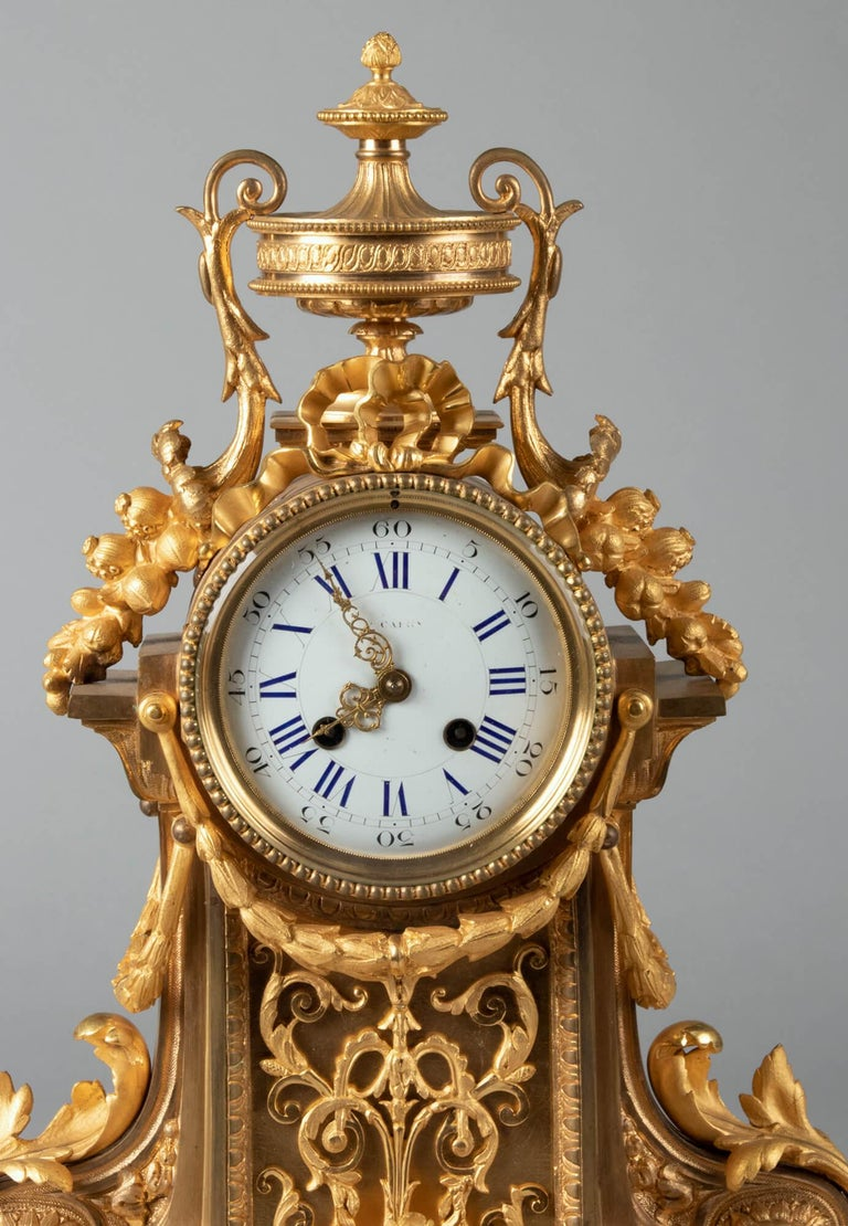 An elegant French ormolu mantel clock in Louis XVI style. The clock is bronze casted and gilded, the dial is enameled. Richly embellished with neoclassical ornaments such as garlands, ribbons and scrolls. The clock dates from the Napoleon III