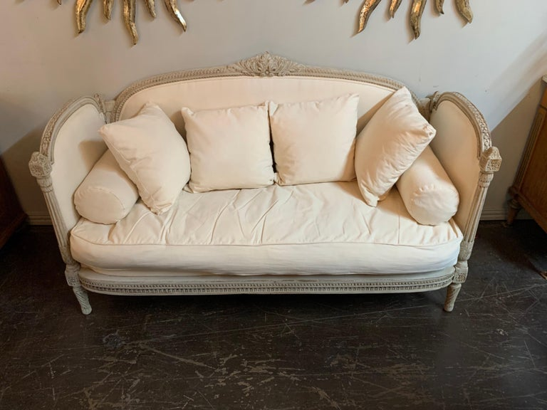 Lovely 19th century Louis XVI style carved and painted sofa. Upholstered in a beautiful creme colored linen. Exceptional carvings and so stylish. Comfortable as well! Better hurry! This will not last long.