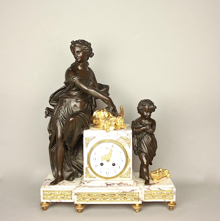 A 19th century Louis XVI style clock garniture, a so called 'Garniture de Chemineé'. The mantle clock with two matching vases constructed of pink veined marble and gilt metal. The rectangular drum case with a finely painted enamel dial, Arabic