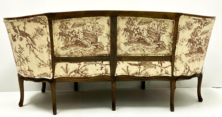 Love this! This is a 19th century Louis XVI style carved walnut French canapé in a chinoiserie linen. It is in very good condition, and the cushion is a nice plump down. The upholstery is recent appears to be a printed cotton- linen blend. The