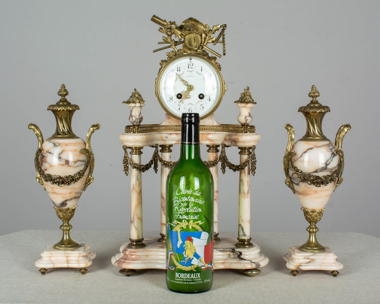 A 19th century Louis XVI style three-piece marble and bronze mantel garniture consisting of a clock and a pair of decorative urns. Clock has an architectural demilune form decorated with cast bronze floral garlands and finials and is surmounted by a