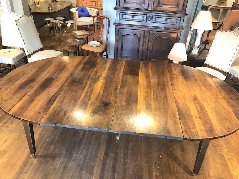 Fine quality 19th century Louis XVI style French Provincial extending dining table. Made of beautifully patinated and very highly figured Circassian walnut with five straight tapering legs and casters. A large oval table extending with two leaves