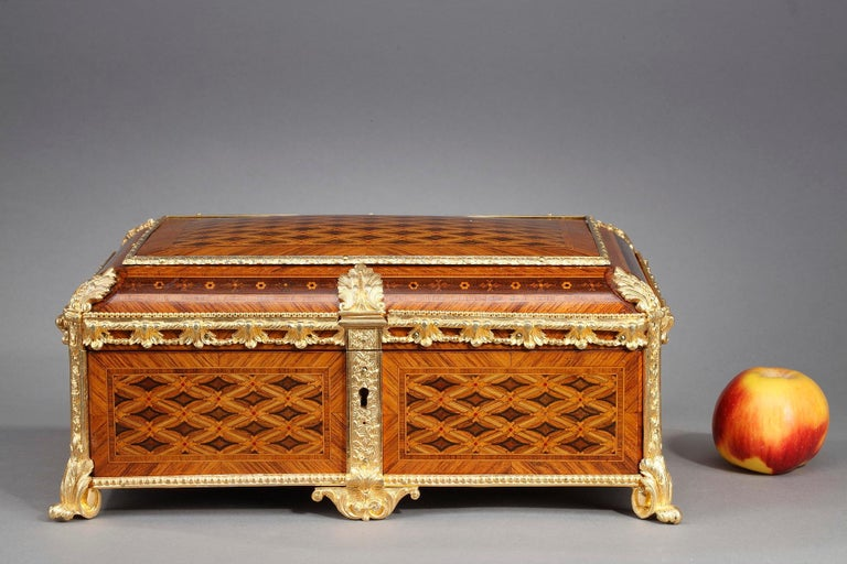 Geometric marquetry pattern and faithful interpretation of the Louis XVI style characterize this 19th-century French jewelry box. Enfolded in intricate marquetry featuring diamond pattern, the casket is mounted in gilt bronze, chiseled with delicate
