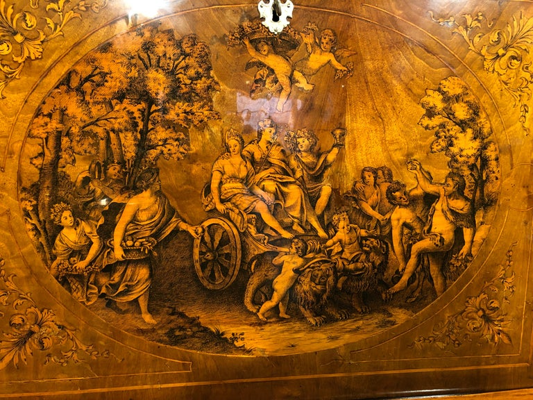 This Italian secretaire, Lombardy region, probably the city of Milan, is a work of art in tarsia, depicting the triumph of Bacchus, impressive in details and in its execution, close to the realism of a painting, inlaid on the sides by beautiful