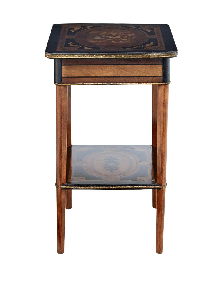 19th century mahogany inlaid ladies work table, circa 1880.  Beautiful multiple wood inlaid top depicting a bird among a branch and florals. Ebonized with borders and swags. Top opens to reveal a fitted interior with partitions and polished brass