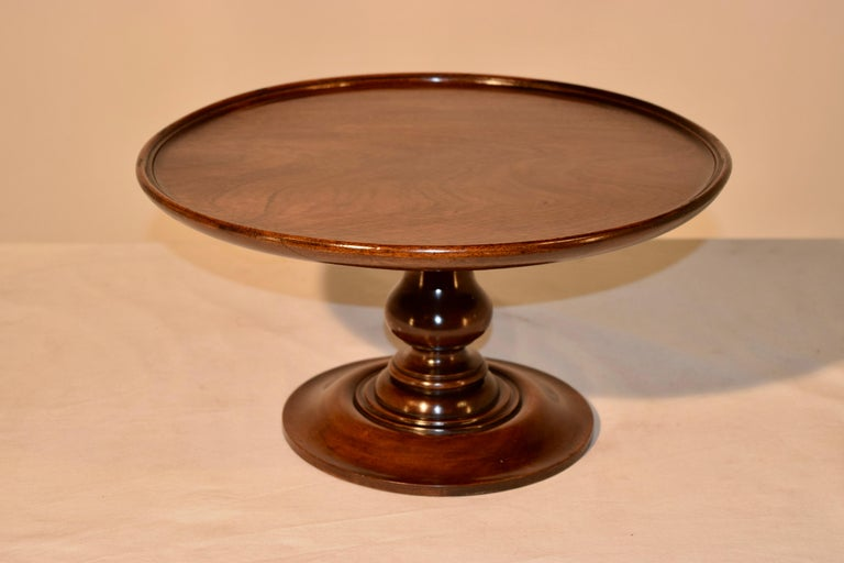 19th century English Lazy Susan made from mahogany with a dish shaped top supported on a nicely hand-turned pedestal base. The top has slight warping from age.