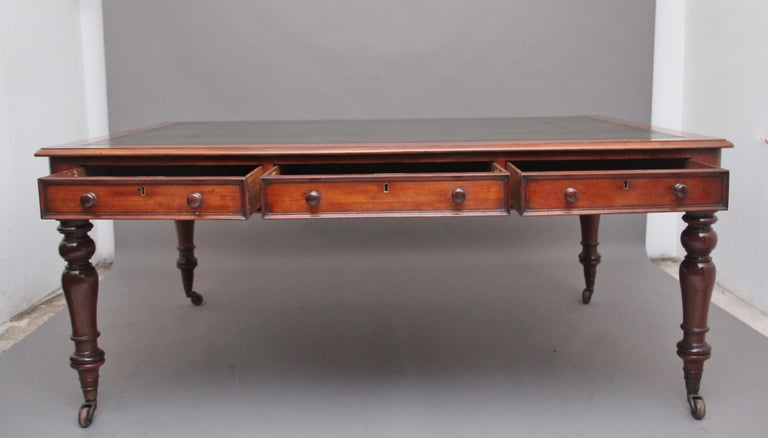 A large mid 19th century mahogany partners writing desk / table, the moulded edge top having a green leather writing surface decorated with gold and blind tooling, having six oak lined frieze drawers with the original mahogany wooden knob handles,