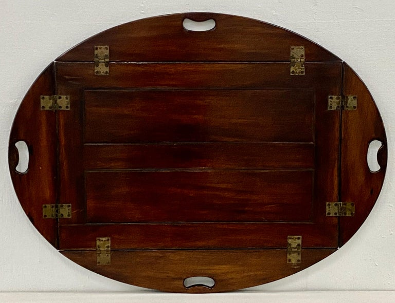 19th century mahogany serving tray  Hand made serving tray from solid mahogany with brass hardware.  The oval tray has four handles along four drop-down sides.  The tray sits atop a folding stand.  Dimensions 39.5