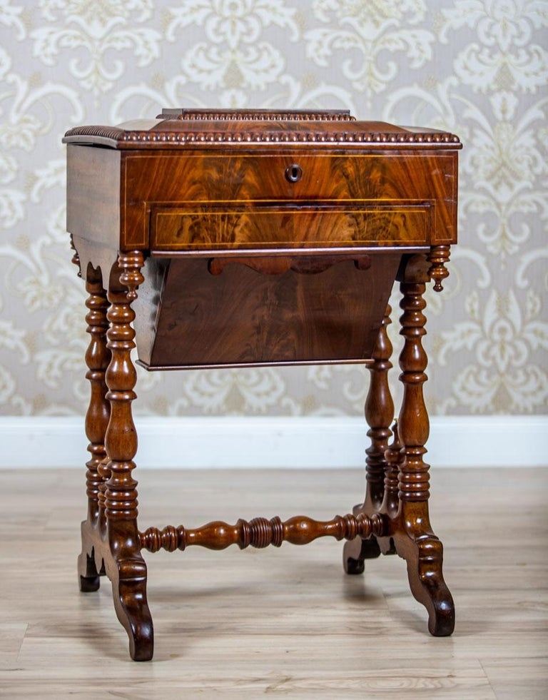 We present you a mahogany sewing table from the second half of the 19th century. The apron is rectangular, with a liftable board, a storage compartment, and two drawers – one narrower and the other one in the shape of a cone, suspended at the