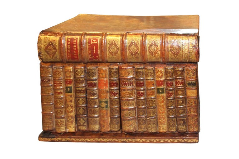 This 19th century tantalus is designed to look like a row of 14 leather bound books, covered by a large book stacked on top. Each book features different decorative detailing. This piece is made of mahogany, and includes an internal lift-out tray