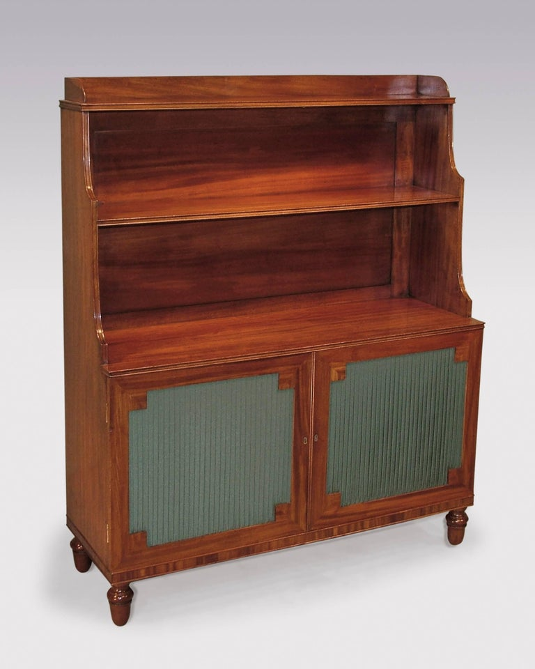 A pair of early 19th century Regency period well figured mahogany waterfall bookshelves, having galleried tops above beaded edged graduated shelves, above pleated panelled doors with mitred corners, supported on turned acorn feet.