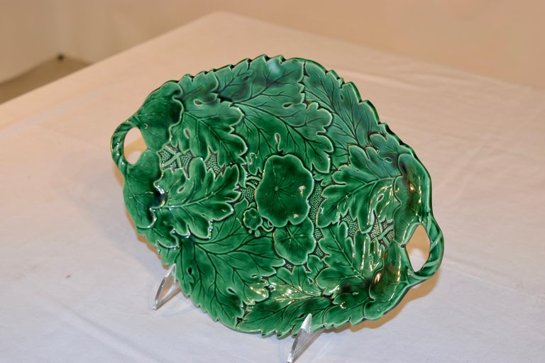 19th century Majolica dish with two handles. The mold is very crisp and shows layered leaves over a stippled background with a lily pad in the center. The dish is shaped around the edges as well for additional interest.