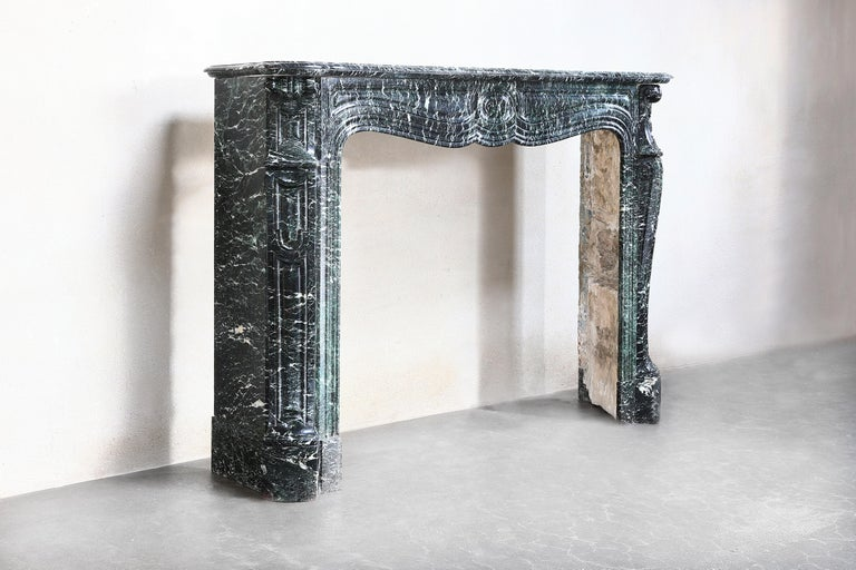 Beautiful antique fireplace made of Vert de Mer marble in the style of Pompadour from 1850-1870. Pompadour fireplaces are recognizable by the rounding in the middle. This is a very charming and stylish mantle made of a special marble type.