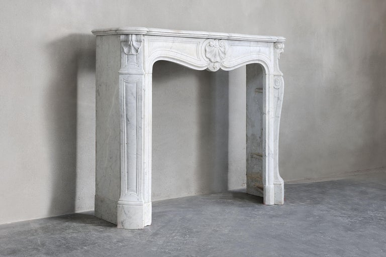 Beautiful antique fireplace of the Italian Carrara marble in the style of Louis XV. This chimney has a compact size, making it suitable for many interiors. The fireplace dates from the 19th century and is equipped with 'trois coquilles' and has